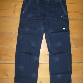 NYE Molo jeans med stjerne indvævet i stoffet. Gennemført kvalitet!  De er super-fede med mange detaljer, bla knapper med dødningehoveder.  Farven er dyb mørkeblå.  Regulerbar elastik i taljen. Lynlås i lommerne. Brunt stjernebånd bagpå.  Bud fra 200 kr. Bytter ikke.  KH ML :-)