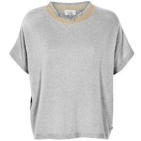 Super fin bluse fra Nümph. Blusen er grå med en guld metallisk tråd i kraven. Den er med korte ærmer og rund halsudskæring. Oversize fit.