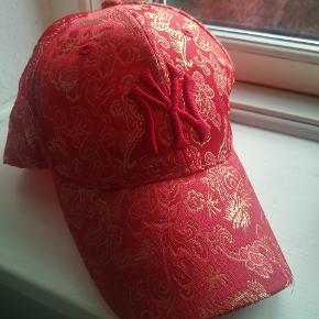 Rød kasket i silkelignende materiale med kinesisk guldmønster fra mærket NY. Kan justeres i nakken efter størrelses behov.  Fremstår i flot stand.