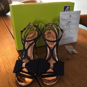 Str. 38  Flotte Ted Baker sandaler i farven Navy blue. Modellen hedder ARAYIS Jeg købte dem til mit bryllup, og har kun været på i 4-5 timer. De har så mange flotte detaljer. Sålerne, den lille sløjfe bag på og andre detaljer er i rosa guld. Der er enkelte brugsmærker nederst på hælen, men der medfølger ekstra af disse, hvis man ønsker dem skiftet.  Original emballage medfølger Derudover medfølger hvad der kan ses på sidste billede.  Nypris: 1.040 ,- Hvis de skal sendes kommer portoen oven i prisen. Sender med DAO