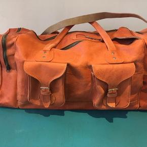 Virkelig skøn rejsetaske/weekendtaske i orange læder og et fint vinrødt for. Købt i en antikforretning.  Tasken måler ca. 25x25x60. Nogle steder er læderet ujævnt i farven, og i bunden stikker et lille stykke af en stang ud (kan ses på billede 3).