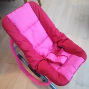 Skråstol kan indstilles i ligge- / siddehøjden, kan vippe frem og tilbage og har bremse klodser på. Har to bærehanke. Betrækket kan tages af og vaskes.
