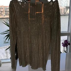 Varetype: Bluse Farve: Guld,   Beige Kvittering haves.  Super flot bluse m. V- udskæring  sælges. Den er i 95 % bomuld. Aldrig brugt. Jeg kan kontaktes på 42422704