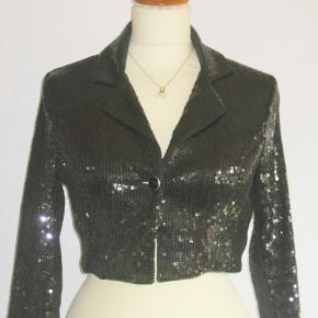 Amisu, New Yorker, Flot og meget speciel fest-jakke. Jakken er med sorte pailetter overalt. Super-FLOT. Jakken har 6 % elastan hvilket giver jakken en dejlig bevægelsfrihed.  Brystvidde: 88 cm Længde: 40 cm  Ingen byt, og prisen er fast