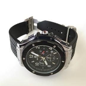 Lækkert og stilfuldt herreur fra Megir sælges nyt/ubrugt. Uret er udstyret med Quartz urværk, hvilket man bruger i mange kendte urbrands.  **Uret er NYT/UBRUGT**  Specifikationer på uret:  - Diameter 52mm - Rembredde 24mm - Udstyret med høj kvalitets Quartz urværk - Remmen er lavet af silicone (25mm bred) - Udstyret med en elegant datofunktion. - Indbygget med ridsefrit mineralglas. - Uret er vandtæt op til 3 ATM (Uret tåler stænk ved almindeligt brug, men er ikke vandtæt til badning). - Ridsefrit mineralglas - Uret kommer i en flot æske med mærker på i folie.  Alt i alt et flot ur af høj kvalitet til prisen.  Kan afhentes personligt eller sendes forsikret med track and trace nr.