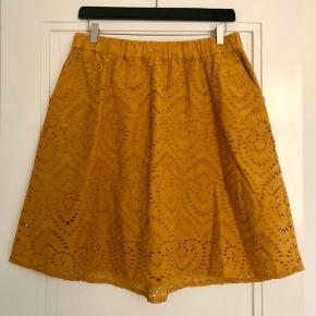 Fineste nederdel i karry-gul farve. Har elastik i livet og to stiklommer. Brugt meget begrænset.  Længde ca. 55 cm.  Livbredde ca. 41 cm.  Bytter ikke!