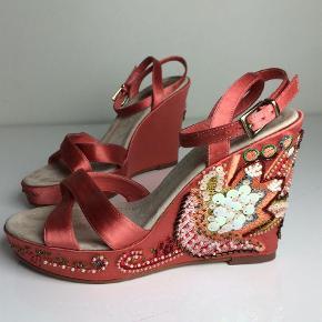 Eksklusive nye sommer sandaler fra engelske RAVEL. Standen er sat til 'god men brugt' da sandalerne har brugspor pga materialet er sart, satin og ruskind, og der har siddet et klistermærke på den ene hæl. De har aldrig været anvendt, udover prøvet på, hvilket også kan ses på sålerne samt hælduppen. Venligst se billeder.  Utrolig smukke med håndlavet perlebroderi på siderne. Jeg vil beskrive farven fersken orange. Perlebroderiet er intakt.  Str 37. Indvendig længde: 24,5 cm.  Kilehælen måler 10,8 cm og plateauet 3cm, så man går kun på 7,8 cm. Kostede omkring 1000 Kroner fra ny·  TSPAY Sendes med DAO 🌸BYTTER IKKE🌸  Se gerne mine mange andre annoncer 🦋