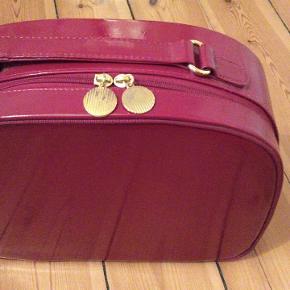"""Fin lille rød/Bordeaux kuffert med dertilhørende pung. Mål: 30x25x10 Lavet af en slags plastik og foret med stof indeni. Det et """"guld"""" lynlås rundt om."""
