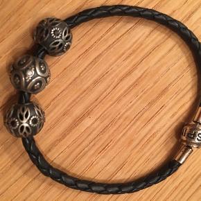 Flot flettet armbånd i læder med sølv smykkelås. På armbåndet er 3 sølv charms.  Alt er ægte 925 Sterling sølv  Armbånd og kugler/perler passer sammen med Troldekugler og Pandora.  Alt sælges samlet. Sender gerne.