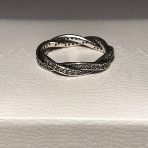 Funklende snoet sølvring fra Pandora med kubisk zirkonia sten. Størrelse 54. Aldrig brugt, så står som helt ny ✨  Tjek min profil for flere Pandora smykker og charms i både sølv, shine og rose 💍  Æsken medfølger ikke.