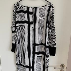 Sort/hvid Mønstret kjole fra Saint-Tropez. Fungerer både med bare ben eller strømpebukser under. 3/4 lange ærmer, som afsluttes med en bred stretchy kant. Str. Small men kan også passes af en medium.