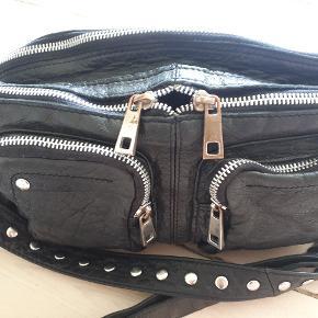 Fin Nunoo crossbody taske i sort med sølv nitter på remmen. Fejler ingenting. Der er brugstegn særligt på lynlys og spænder. Ingen huller.