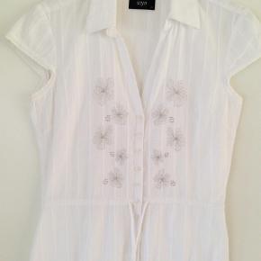 Varetype: Kortærmet Farve: Hvid  Super fin skjorte  Blomsterne er broderet med tynd tråd  Længde 59 cm.  Brystvidden 88 cm.  100 % indisk bomuld   Mobil Pay. / Ts