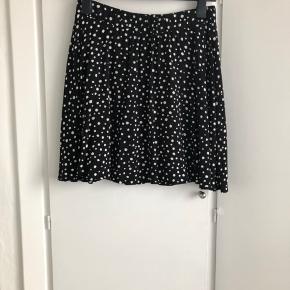 Nederdel fra Vero Moda i sort med hvide polkadots og elastik i taljen. Længde er 46 cm, og livvidde er 78, når elastikken ikke er spændt ud.  Vaskeanvisning mangler, men vaskes på 30 grader. Jeg sender gerne med DAO for 36 kroner.