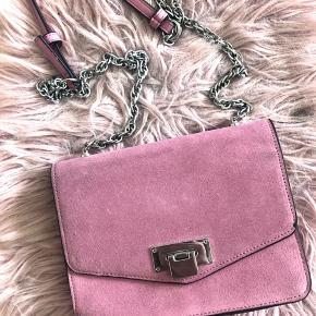 Rosa taske med sølv kæde og en lomme inden i.