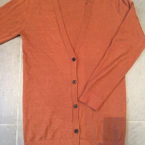 Rigtig fin cardigans flot rust farve med 50 % uld og 50 % akryl. Str. M. Den er mellem lang så går ned over bagdelen.  Den er brugt 4-5 gange og vasket en enkelt gang i uld vaskemiddel.