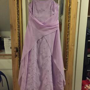 Fin festkjole fra Jora Kid's i str. 12. Kjolen er lys lilla og har små broderinger med skinnende perler. Tilhørende tørklæde.  Kjolen har hængt i et skab i en del år, men er så god som ny, aldrig brugt og fra ikke-ryger hjem :-)