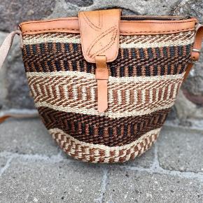 Smuk, håndlavet sisaltaske med detaljer af ægte læder. Læderremmen kan justeres til den ønskede længde. Åbningen på tasken er ca. 30 cm. Den er foret indvendigt og der er lynlås i toppen.   Se flere tasker på min profil i forskellige designs og størrelse.   Taskerne er købt på lokale markeder i Kenya.  Varen kan sendes med DAO eller afhentes efter aftale.   # Crossbody taske, Afrika, Kenya, sisal, unik