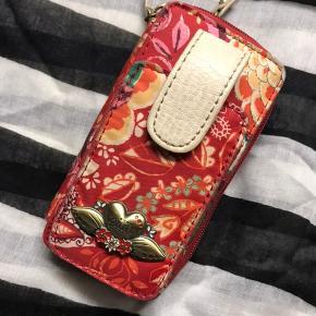 Fin lille mobiltaske til pigens første mobil.  Remmen trænger til at bliver glattet ud, men fejler intet.