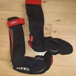 ZONE3 svømmesokker, 2 mm i slidstærkt, højelastisk neopren til brug ved sbømning åbent vand så fødderne holdes varme. Til helårsbrug.   De er tætsiddende med ekstra længde op af benet.  Størrelse S (38-39)  Aldrig brugt. Købt på watery.dk.
