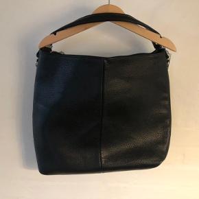 Super fin lædertaske - helt ny - stadig med mærke.  Tasken har både kort skulderstrop, samt lang skulderstrop.  Der er flere rum inden i tasken, samt en lomme på siden med lynlås.