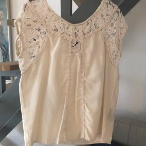 Silke/bomuldstop fra Stella Nova med mange smukke detaljer i lækker cremefarve. God både til jeans og nederdele. Brugt ganske lidt og naturligvis helt uden fejl eller pletter. Brystmål 50 og længde 55 cm.