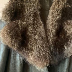 Smuk læder frakke med en stor og lækker pelskrave. Knappe lukning.