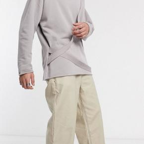 Sweatshirt med rå kanter og fed rem-detalje. Brugt 2-3 gange. Farven er lys grålilla.  Byd endelig!