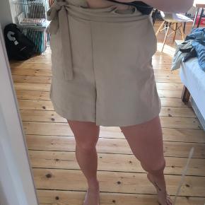 Nederdel med slå om look foran og lynlås i siden. I lidt tykt materiale
