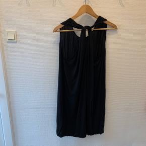 Let kjole i lækkert blødt materiale med tvist på ryggen ved skulderbladene. Kjolen kan bruges med eller uden bånd i taljen. Der er små diskrete løkker til bånd/bælte, men dette følger ikke med. Lille i størrelsen.