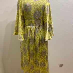 Virkelig smuk og lækker Baum und Pferdgarten kjole i lys gul med flot mønster af blomster og sommerfugle. Kjolen har været brugt til en lejlighed og fremstår derfor i super stand. Kjolen er skåret under brystet med en lille lilla detalje i overskæringen og har lynlås i siden. Kjolen er lavet i 100% silke og er derfor skøn at have på☺️