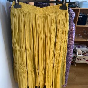 Karry-farvet plisseret nederdel, brugt få gange.