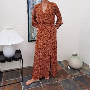 """Skøn kjole i """"brændt orange"""" med sorte """"dots"""". Kjolen er i viscose og har lange ærmer, dyb V-udskæring, overskæringsstykke i livet med små læg under barmen, som i fællesskab giver kjolen facon og et feminint udtryk. Kjolen har lynlås i siden og en slids i siden. Til salg i flere grupper!"""