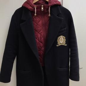 Sælger denne Tommy Hilfiger frakke, modellen hedder icon wool and nylon coat i farven midnight.  Der medfølger aftagelig hætte som kan knappes på.  Købt den 3/3-2019 i Tommy Hilfiger butikken på Strøget i København. Kvittering og knap medfølger. Str 2 svarer til en størrelse small Nypris 2600kr