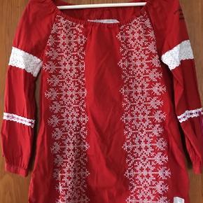 """Smuk rød tunika med broderier i størrelse 1. Blusen har desværre et lille """"klip"""" et sted på forsiden. Se billede 3, som er lidt overbelyst. Det har ikke """"udviklet"""" sig i brug og vask, og ses næsten ikke. Sælger kun, fordi den er lige det strammeste over overarmene."""