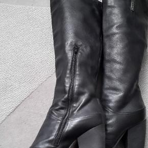 Langskaftede støvler i blødt skind med 8 cm hæl, lynlås på indersiden og 2 dekorative lynlåse på siden. Købspris 1.800 kr. Støvlerne er brugt kun en enkelt gang (købt for store i str.) og lige som nye.