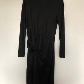 Smukkeste Malene Birger kjole i sort med draperet folder henover  mave og ryg.   Har to små huller, hhv. for og bag under folden som vist på billedet. Dvs. det er ikke huller, som på nogen måde er eller bliver synlige ved brug af kjolen.   Der er selvfølgelig taget højde for de to huller ved prissætningen.