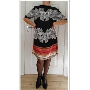 Bytter ikke! Mp. 775,- . Eksklusiv porto. Fantastisk smuk multiprintet kjole fra Gustav, str. M. En kjole der kan bruges til alt. Kjole fremstillet i en skøn silke/viscose-kvalitet, der falder flot. Løstsiddende model med korte ærmer og ribkanter. Lukkes på ryggen med lynlås. Farve: Sort bund med smukke farver, se billederne. Stof: 68% Viskose og 32% Silke. Løstsiddende. Gustav størrelsesguide str. 38: Bryst mål 92 cm Talje mål 76 cm Hofte mål 100 cm  For og ryg stykket målt ved bryst linjen 106 cm. Længde 98 cm. Købspris kr. 1.500,- Modellen på billederne er str. 38, højde 167cm. Hænger i dragtpose. Kommer fra et ikke ryger hjem.