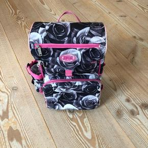 Fin skoletaske fra Jeva, i grå/rosa rosen-mønster. Indeholder stort rum til bøger, herunder et separat rum til iPad, desuden et rum til penalhus, samt et termo-rum til madkassen, og på siden en lomme til vandflasken. Idrætstaske og penalhus medfølger.