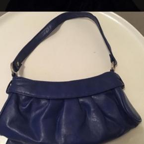 Kobolt blå / Electric Blue lille håndtaske i 'imiteret skind' / PU. Købt på en rejse (25 euro - knap 200,-) og brugt en gang. Mål: Bredde ca 25 cm og højde ca 11 cm. Der en lynlås lukning og lille lomme indeni - også med lynlås, rem måler ca 40 cm. (Påsyet sløjfe foran)
