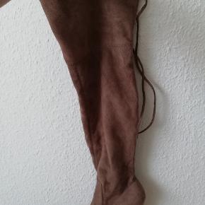 Hælen måler 9,5 cm. De er 20 cm brede øverst, de kan dog snøres ind med bindebånd. Længden på hele skoen er 61 cm. De er blevet brugt en enkelt gang ganske kort.
