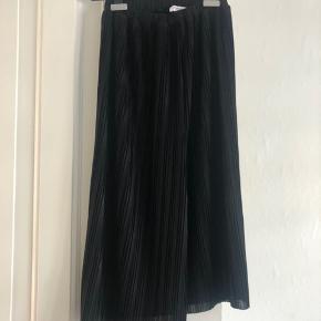 Lang sort plisseret nederdel med glimmereffekt. Aldrig brugt. Pris eksl fragt.