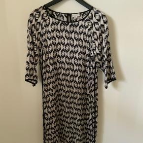 Smuk kjole fra Dea Kudibal i silke str. M i farverne grå/sort. Fra ærmegab til ærmegab måler den 51 cm. Ryg længde er 93 cm.
