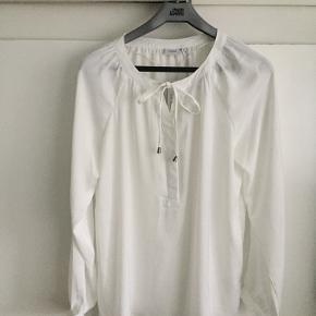 Sød bluse - desværre for stor til mig. Farven hedder antique (helt lys farve - ikke hvid). Længde 70-71 cm. Lukkes med 2 knapper og bånd foran