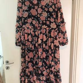 Lang blomstret kjole med tilhørende sort underkjole og bindebånd. Sælges billigt da det er en kollektionsprøve.
