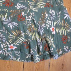 Kort mønstret nederdel, let skråt skåret i en mat grøn farve. Str. M fra Zizzi. Brugt og vasket enkelte gange.  Pris: 75,- pp.  Kan afhentes hos mig i København NV, eller sendes med DAO. Se også mine mange andre annoncer og spar ved køb af mere :)  #30dayssellout