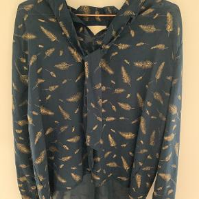 Flot mørkeblå bluse med guldfjer og bindebånd i halsen.  100% Polyester Dress no: 17405 Styleno/name: 5002 Bill Blouse
