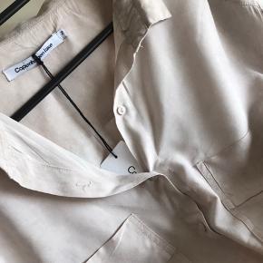 Lækker stor skjorte den har et rosa skær meget lækkert blødt stof som falder rigtig flot