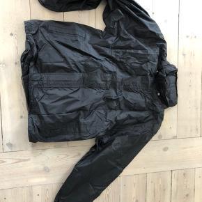 Kilmanock regnjakke til herrer. Str L.  Kan pakkes sammen i en pose, der er integreret i jakken.  Med elastik og velcro i ærmerne. Kan også snørres ind omkring livet. Med hætte.   Aldrig brugt.  Nypris 400.   Kan afhentes i Odense C eller sendes med DAO (37 kr - køber betaler)