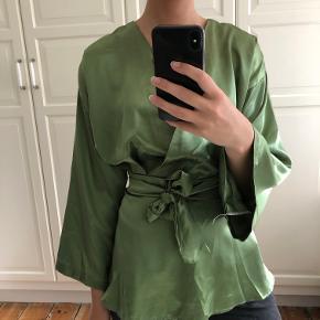 Info: smukkeste satin/silke agtige materiale, kimono-top med bindebånd i flot, lækkert stof. Fik den syet på bestilling, perfekt til fest eller finere lejligheder. Pris: 230 kr. Nypris: 450 kr. Mærke: ukendt Stand: brugt meget få gange Størrelse: small/36 Andet: passer en ganske normal 36, og er syet derefter. Fragt: Jeg foretrækker at sende med tracking (evt. Dao for kun 33 kr.) men kan også møde ved Nørreport.  OBS: Varen kommer fra et røgfrit hjem. Hvis du gerne vil se den først, skal du være velkommen til at mødes i indre by/Nørreport, København. Jeg tager ikke flere billeder end dem på annoncen, og jeg forbeholder mig retten til ikke at besvare kommentarer ang. overstående allerede besvarede spørgsmål. (Eksempelvis kan det ske, at jeg ikke svarer hvis der bliver spurgt om bytte og at jeg allerede har skrevet tydeligt, at jeg altså ikke bytter. Det tager tid at besvare, men kun et sekund at læse sig frem til. Derimod må du/i selvfølgelig altid spørge!)